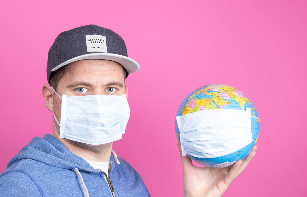 A man wearing a medical face mask, holding a globe that also has a medical face mask on.