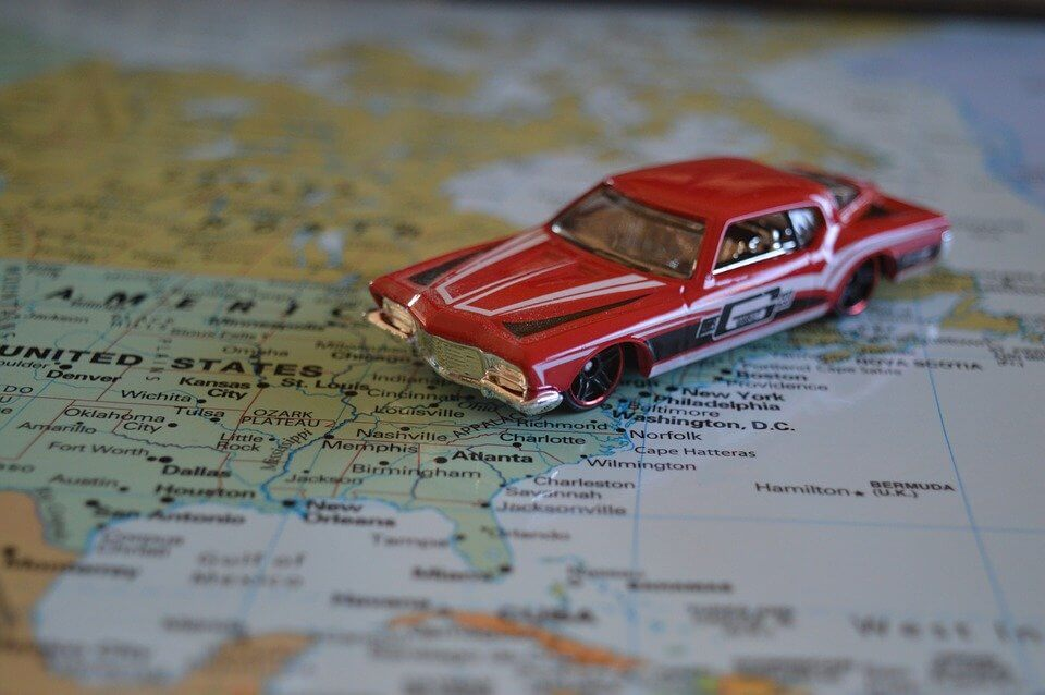 Image of a small red car on a map of the U.S.