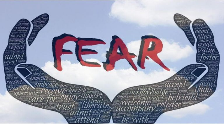 """Image of hands embracing the word """"FEAR,"""" symbolizing managing fears."""