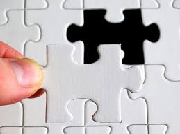 a white puzzle with a hand placing the final missing piece in the open space