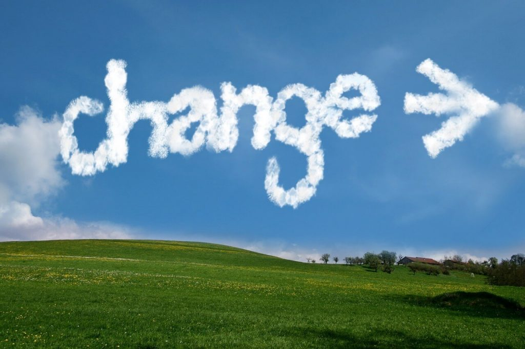 "Image of a countryside with the word, ""change"" across the sky in cloud letters."