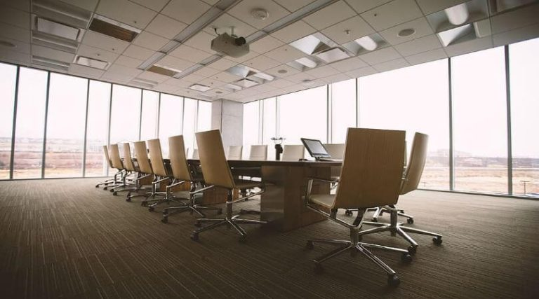 Image of an empty chairs in an office conference room, representing a layoff or furlough.