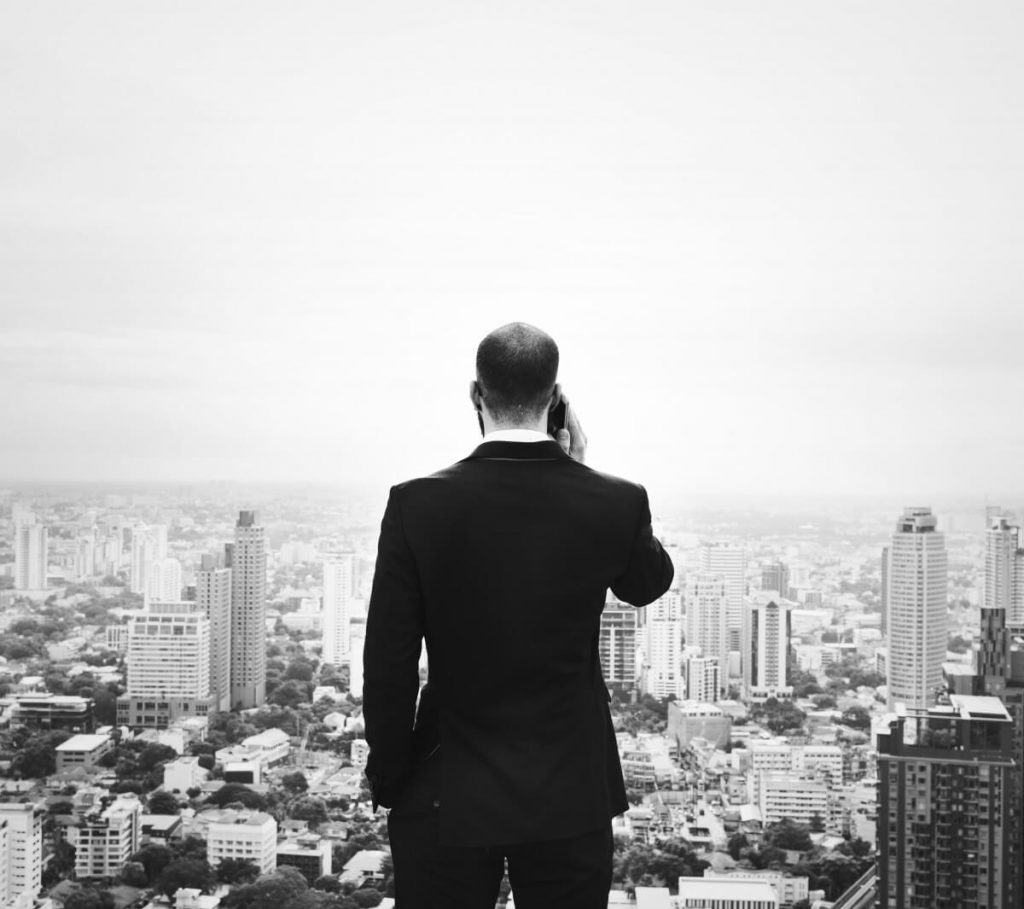 Photo of a man in a suit holding a cell phone and looking out at a city.