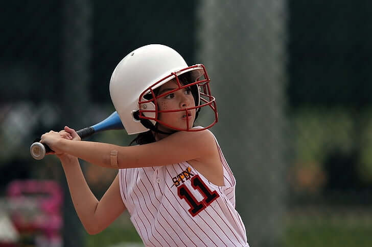 Image  of a young girl at bat, standing in her ready position, wearing a helmet, and bandage on her elbow.