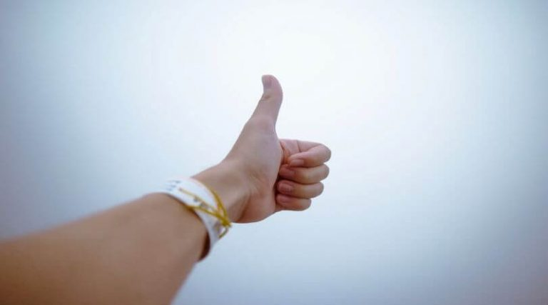 Photo of a an arm extended with a thumb up.