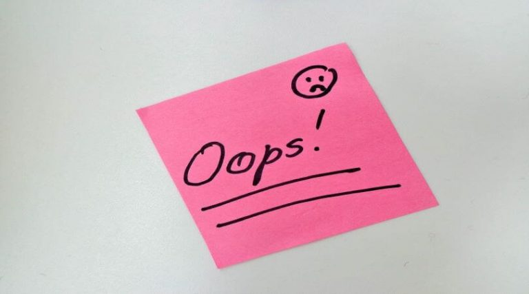 """Image of a sticky note with the word """"Oops!"""" and a frowny face, indicating payroll mistakes."""
