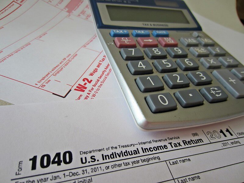 Photo of a calculator sitting on top of W-2 and 1040 forms, which are part of payroll resources.