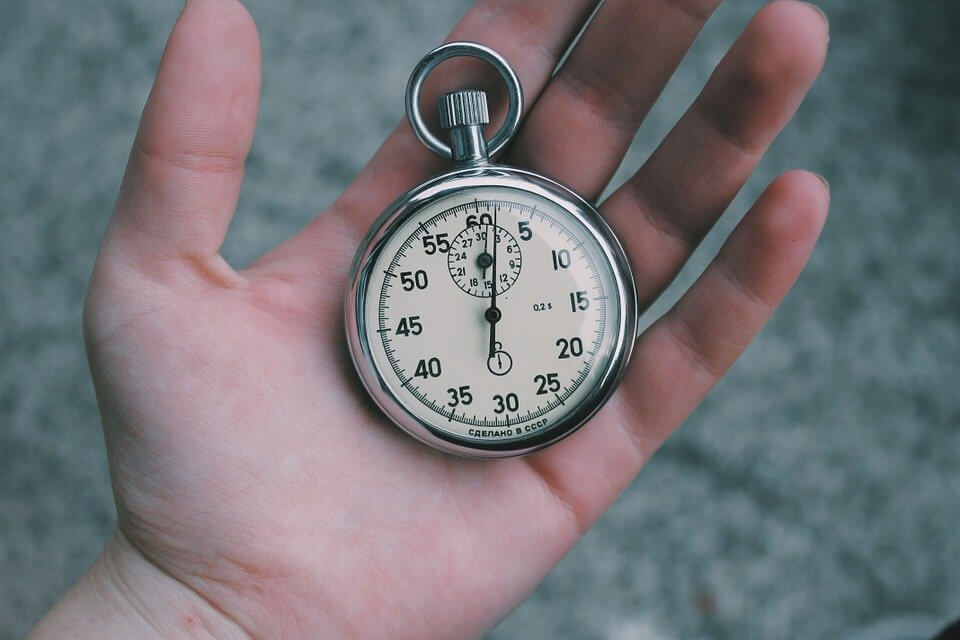 Photo of a hand holding a stopwatch, symbolizing the time needed to get payroll resources.