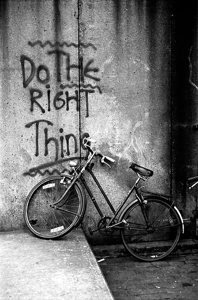 """Photo of a bike leaning against a wall with """"Do THE RiGHT Thing"""" [remember your job safety during protests] sprayed in graffiti on the wall."""