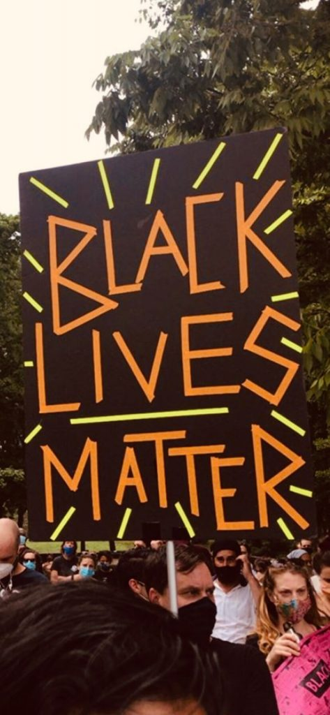 """Photo of protesters exercising their rights peacefully and protecting job safety during protests by holding a sign that says, """"BLACK LIVES MATTER."""""""