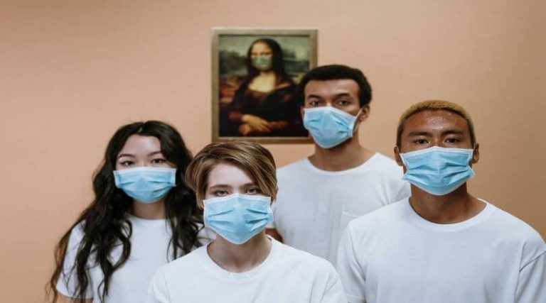 Photo of four people wearing face masks and ready to help.