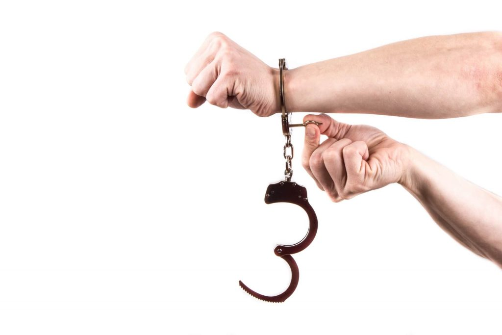 Image of hands unlocking handcuffs off one wrist, as a metaphor for helping.