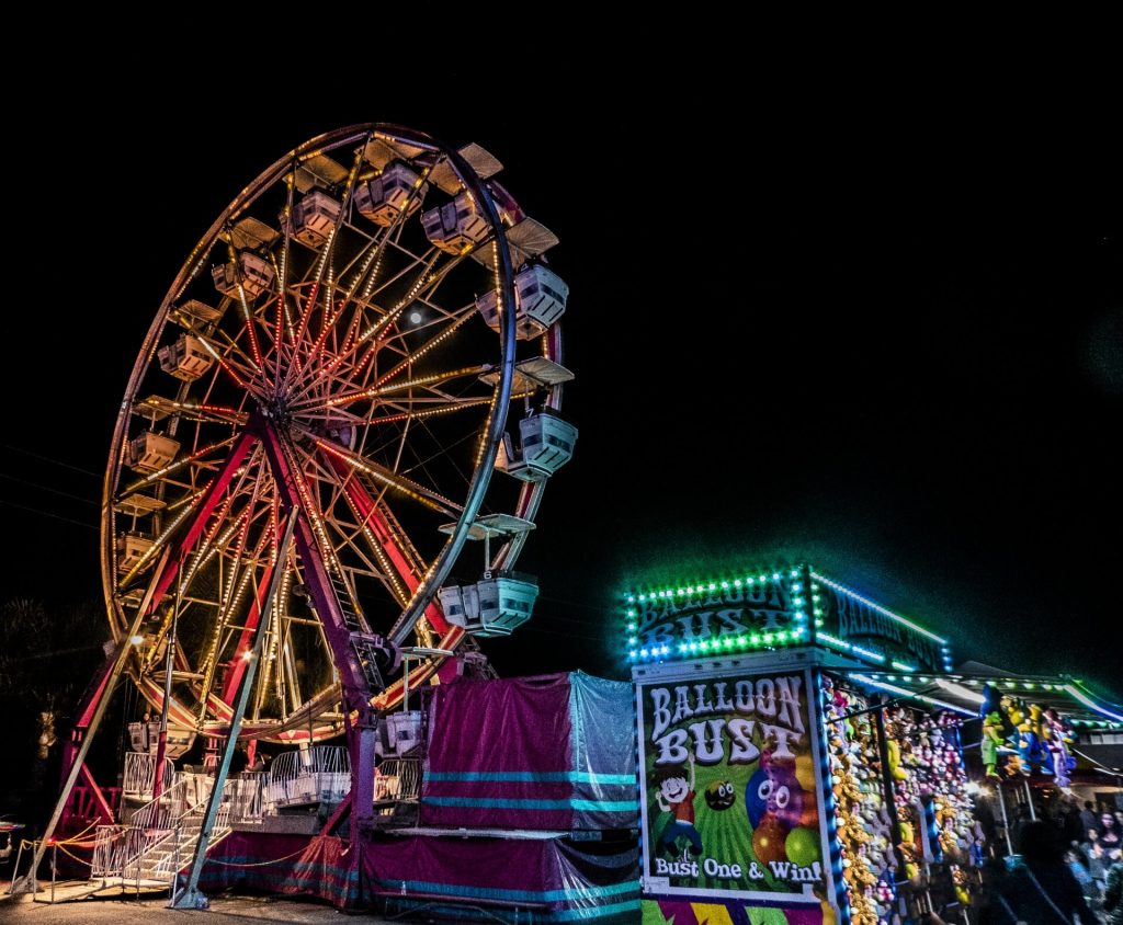 Image of a ferris wheel at a carnival at night.