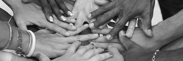 Hands of different genders and races stacked together
