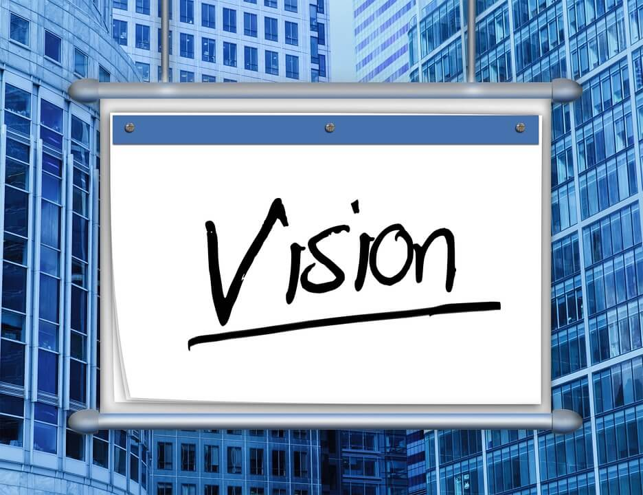 Image of a rolescreen suspended among highrise businesses with the word Vision written in black ink.