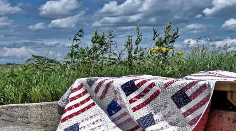 Photo of an American flag quilt out in a wild flower field.