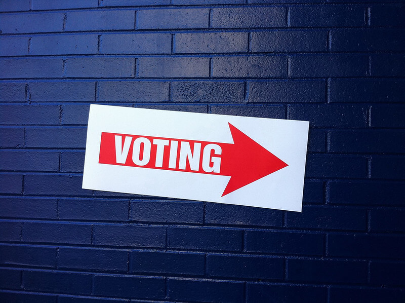"""Photo of a sign with a red arrow and the word """"VOTING."""""""