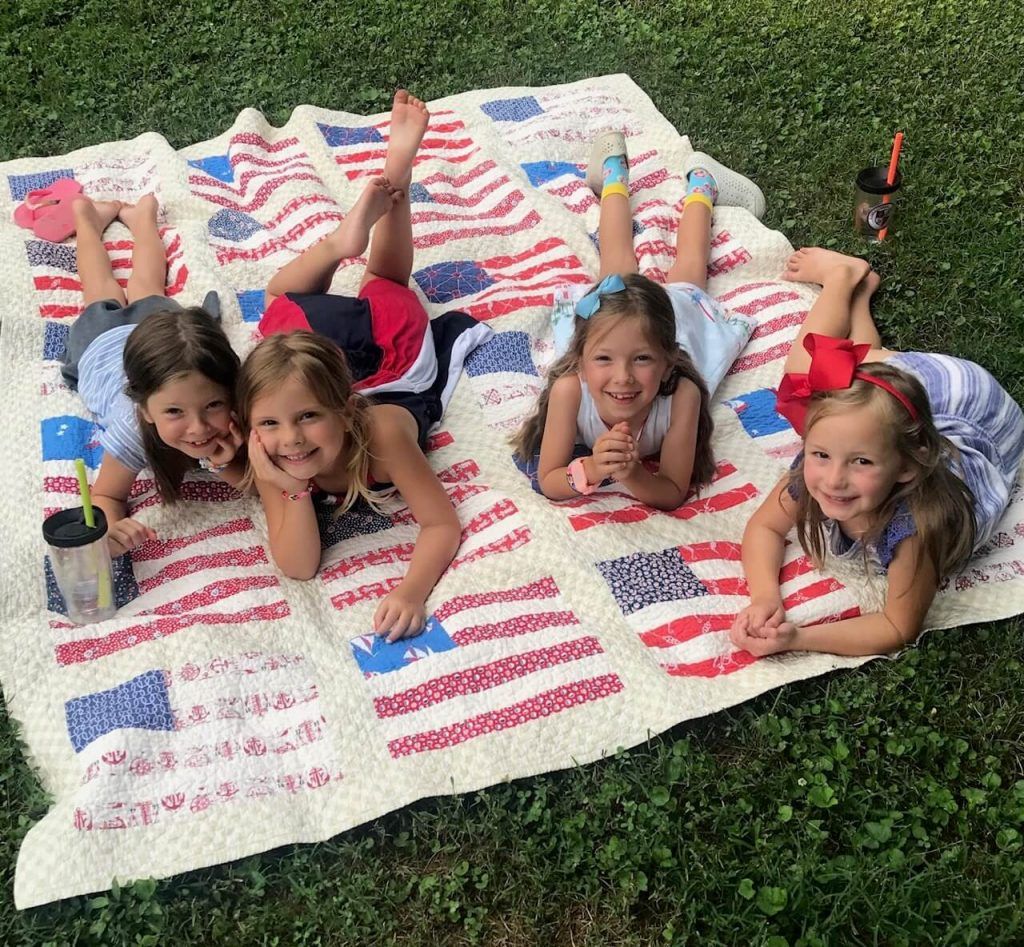 Photo of four girls on an American flag quilt.