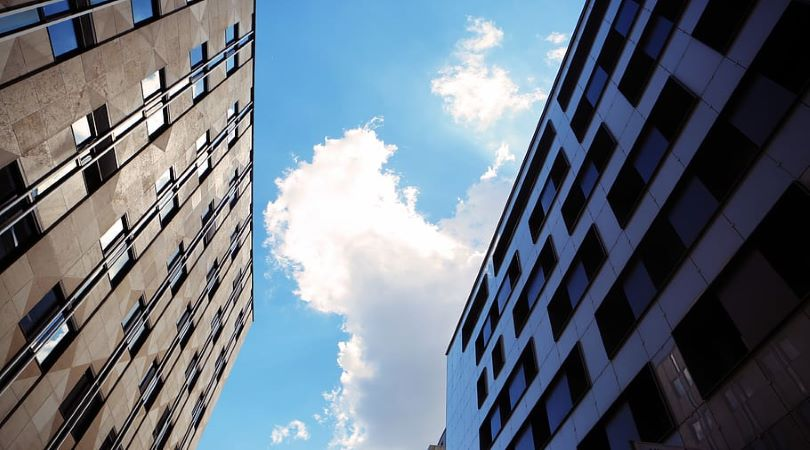 Image of two buildings and a blue sky, with one building dark and the other light, representing a positive attitude.