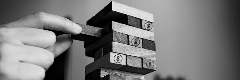 A hand removing a Jenga Block from a stack - financial restructuring is like Jenga