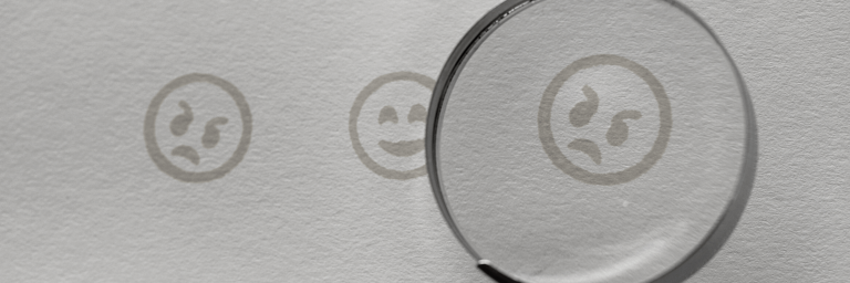 how to respond to negative reviews includes studying them. An image of a magnifying glass over an angry face.