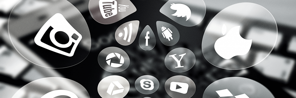 Social media icon bubbles coming out of a cell phone.