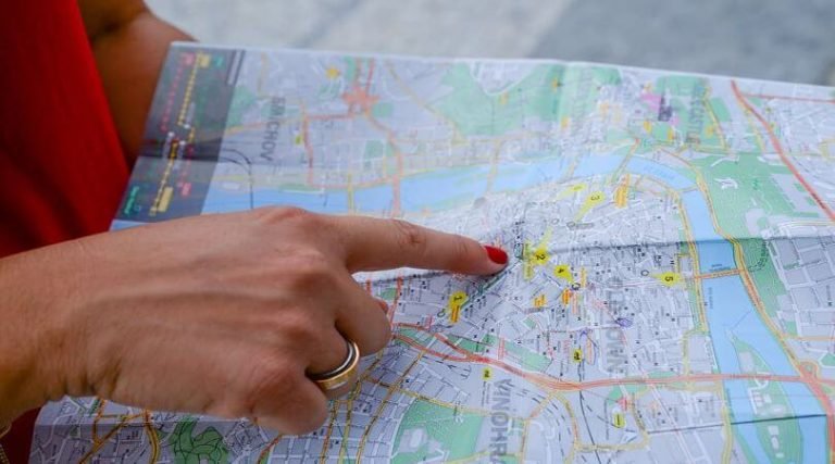 Image of a hand with red fingernails pointing at a spot on a map, as she thinks about working remote and withholding requirements.