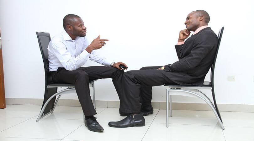 Image of two business men sitting in chairs and talking politics in the workplace.