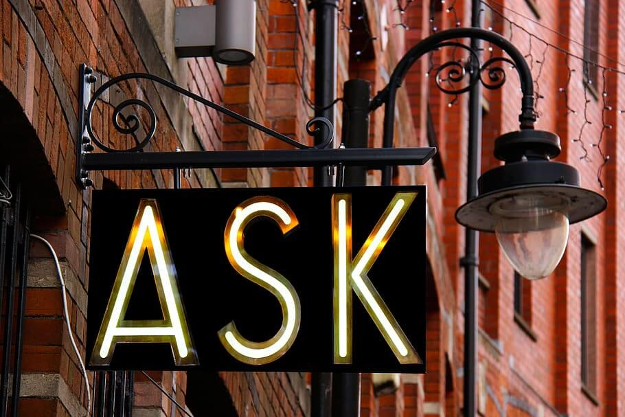 Photo of a sign with the word ASK lit up.