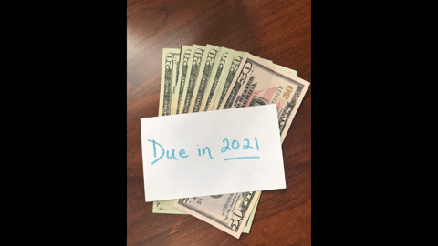"""Image of cash with a note with the words """"Due in 2021"""" written on the paper in blue, referring to the Social Security tax deferral."""