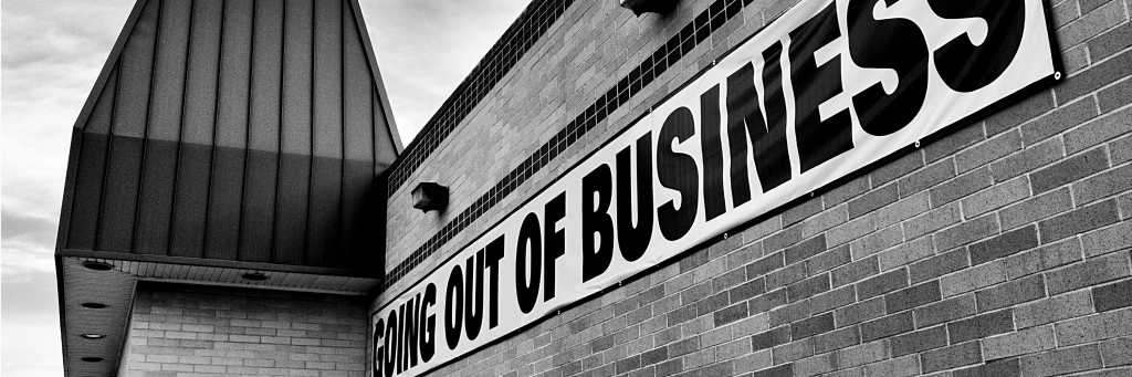 """A business with a """"going out of business sign"""" on it"""