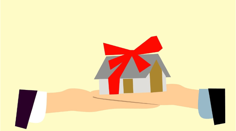 Image of a hand giving back to another hand with a house tied with a red bow in between.