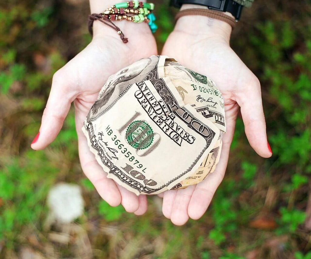 Image of two hands outdoors holding a ball of 100 dollar bills.