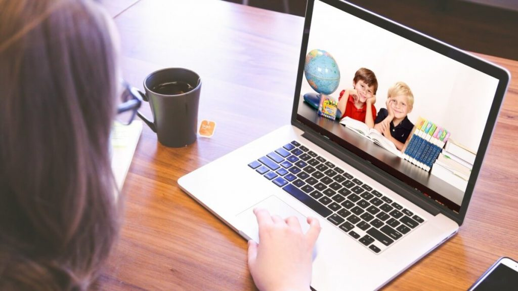 Photo of a teacher on a laptop with students from her virtual class looking at her, as trends show an increase in options for education in 2020.
