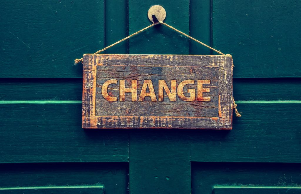 Photo of a wooden sign hanging from a door with the word CHANGE carved into it.