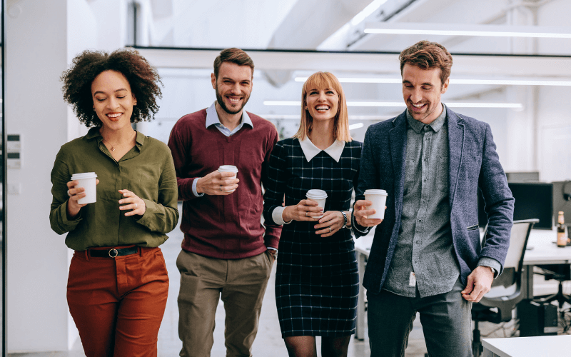 four young professionals holding cups of coffee and smiling