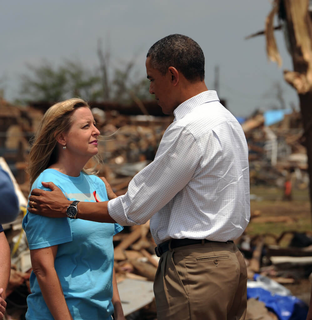 Photo of a leader talking with a woman after a storm.
