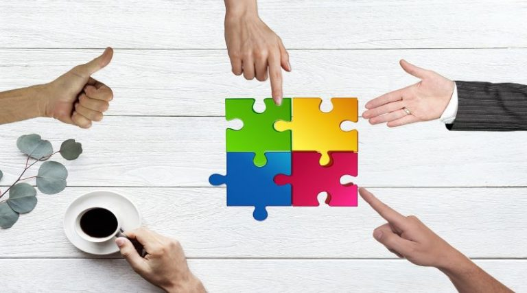 Image of team building during COVID, with employee hands putting together different colored pieces of a puzzle.