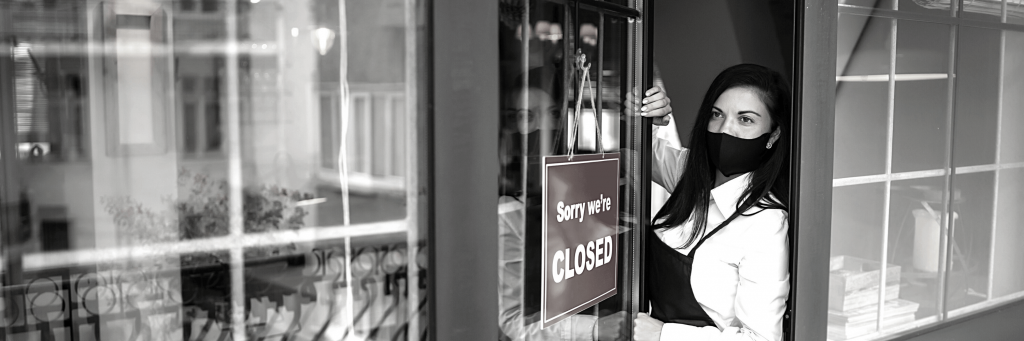 """A woman standing in the doorway of a business, putting a """"sorry we're closed"""" sign on the door."""