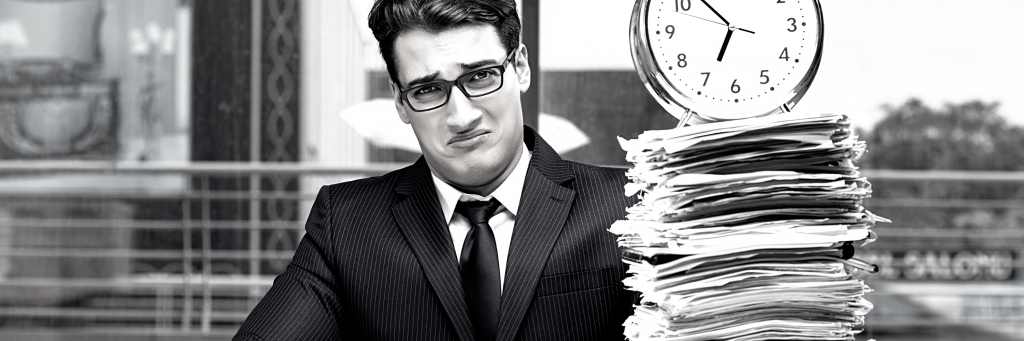 A businessman sitting behind a stack of paperwork with an alarm clock on it, looking sad.