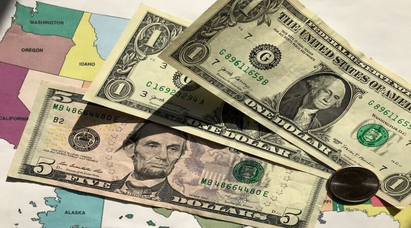 Image of $7.25 (which is the federal minimum wage) cash sitting on top of a U.S. map.