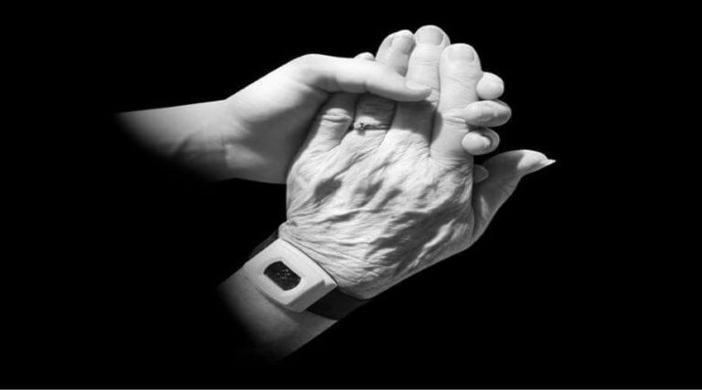 Photo of a young hand holding an older hand, which is wearing a watch.