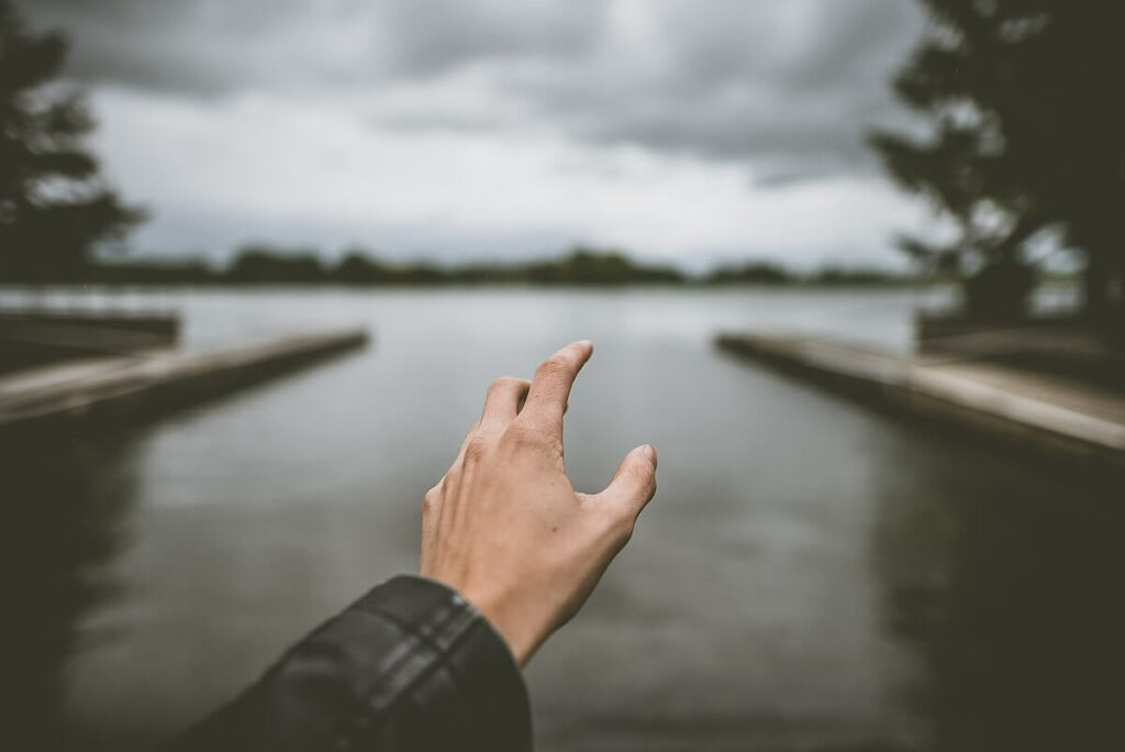 Photo of a hand reaching out to a backdrop of a body of water with trees surrounding it.