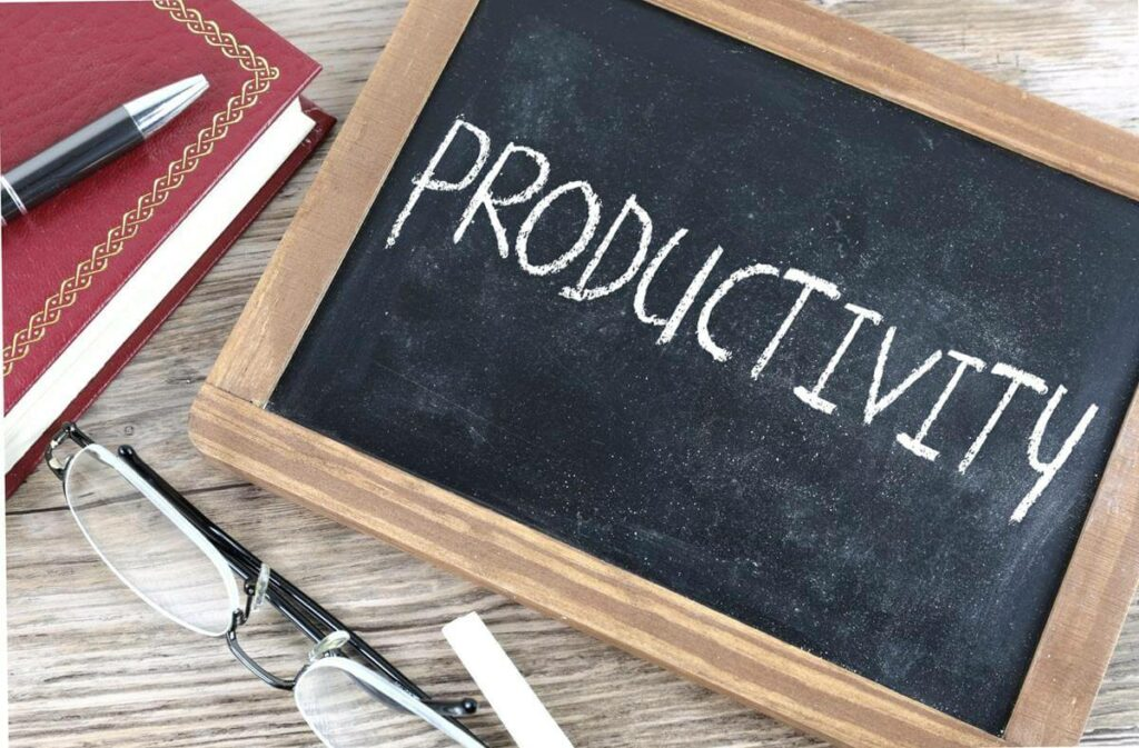Photo of a book with a pen on top, a pair of glasses, and a chalk board with the word PRODUCTIVITY, since compensating employees for vaccinations can help improve health, and consequently productivity.