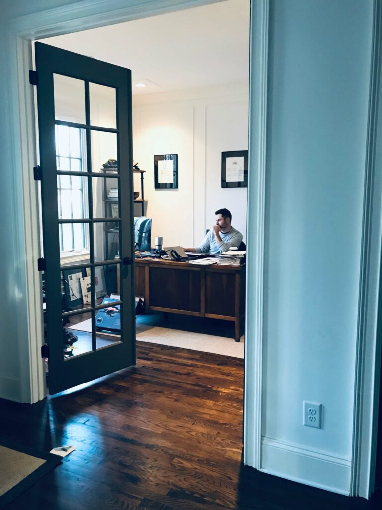 Photo of a man sitting at a desk, working in his home office.