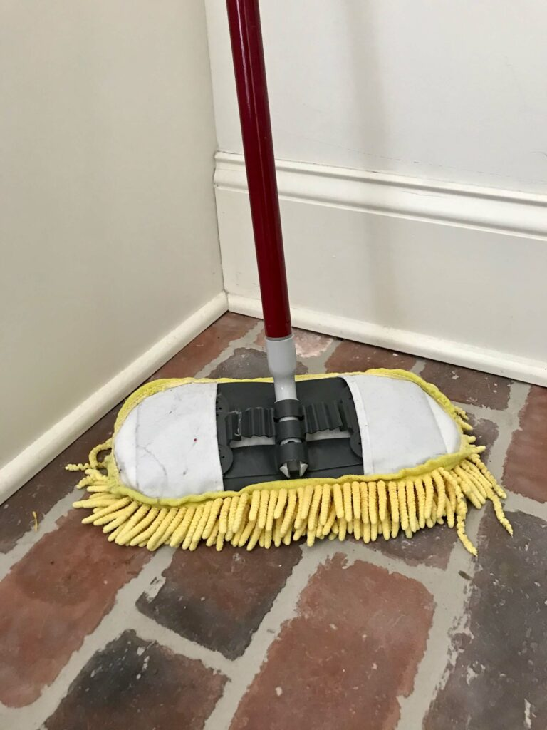Image of a yellow mop on a brick floor.