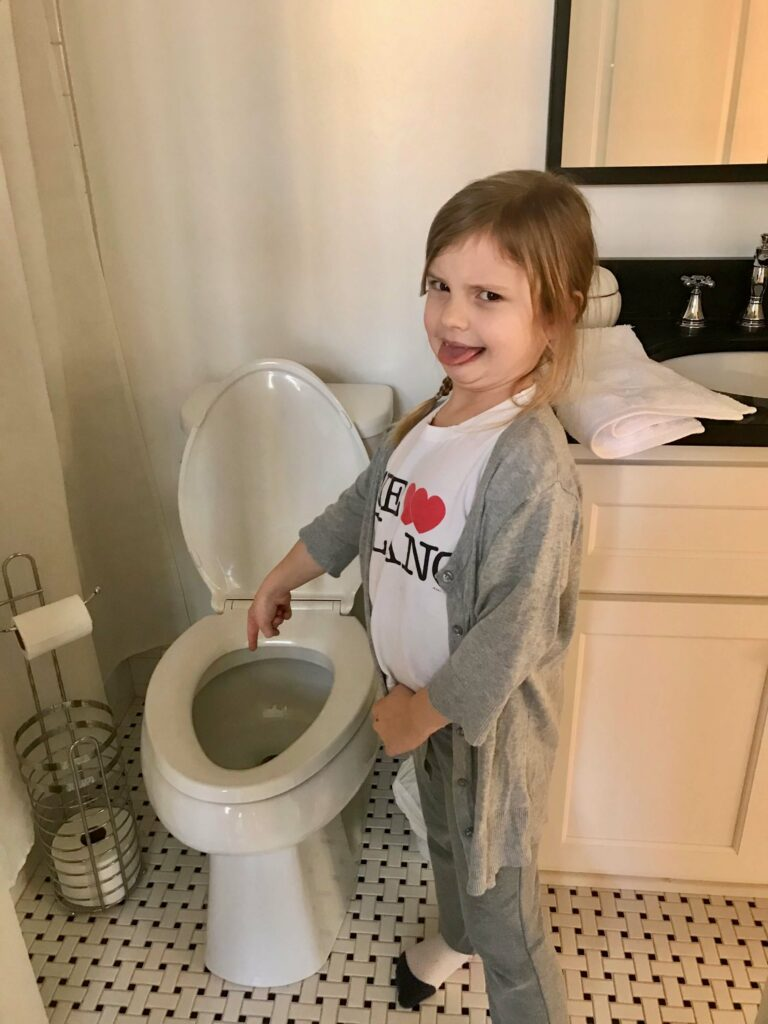Photo of a young girl pointing at a toilet with a disgusted look on her face.