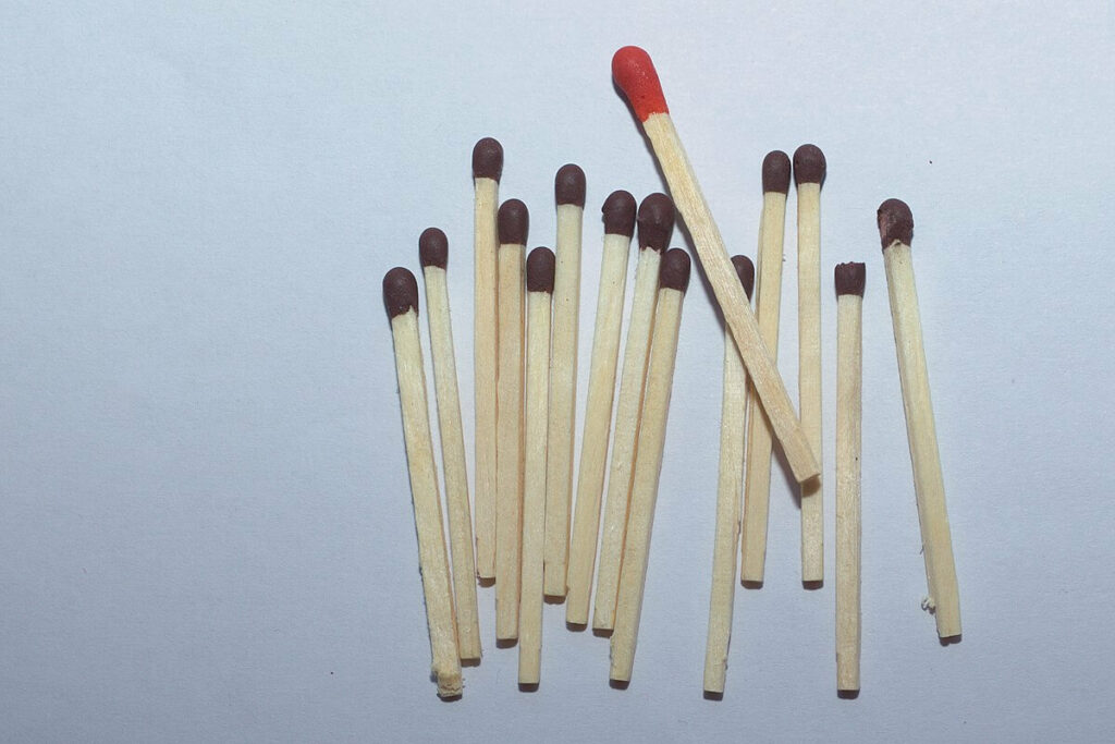 Photo of a bunch of matches-- most of them with black heads, and one with a red head.