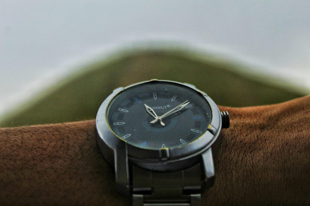 Image of a black wristwatch on a wrist, as a symbol of a temporary worker.