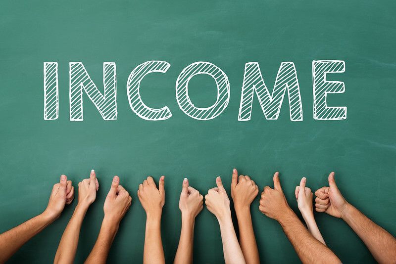 Image of the word INCOME written on a chalkboard, with a bunch of hands giving a thumbs up.